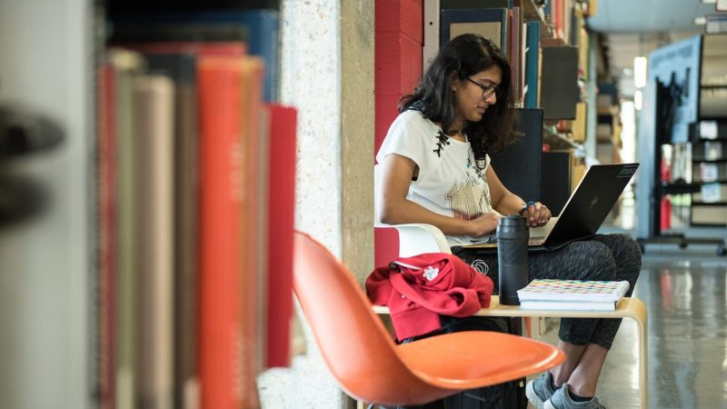 Female student studies in stacks with laptop